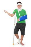 Male with broken arm and crutch presenting Stock Image