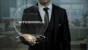 Male broker, head of crypto currency startup shows words Bitcoin Gold on his hand. stock video