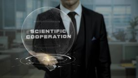Male broker, head of crypto currency startup shows words Scientific Cooperation on his hand. Entrepreneur in suit holds cyber Earth hologram, presenting stock footage