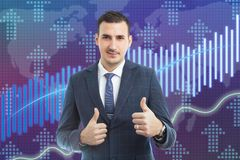Broker showing double thumbs up as rise in stock market graph. Male broker showing double thumbs up and smiling as rise in stock market graph approve gesture stock photo