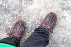 Male Brown Shoe wear  walking. Image of a man`s legs and feet wearing black jeans and brown leather shoes.select focus Brown Shoe Stock Photos