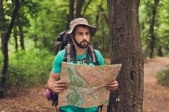 Male brunet bearded confused tourist got lost in the forest, holding map, looking far, trying to find the way. He has a backpack,. All needed for overnight stay Royalty Free Stock Photography