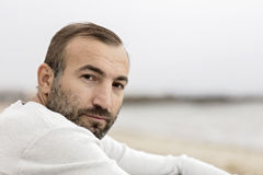 Male (brunette) with a beard in a white sweater looking at the s. Ea. Selective focus Royalty Free Stock Photography