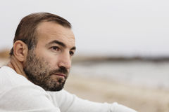 Male (brunette) with a beard in a white sweater looking at the s. Ea. Selective focus Stock Photos