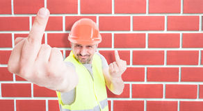 Male builder acting sarcastic. And showing both middle fingers gesture as offensive behaviour concept with advertising area Royalty Free Stock Photos