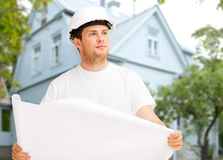 Male builder or architect in helmet with blueprint Royalty Free Stock Images