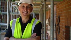 Male builder on construction building site standing on scaffolding with a arms folded laughing and smiling to camera stock video