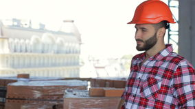 Male builder corrects his hard hat at the building under construction. Side view of male builder correcting his hard hat at the building under construction stock video