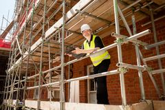 Male Builder Foreman or Architect on scaffolding royalty free stock photo