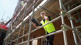 Male builder foreman construction worker on building site wearing a hardhat writing on clipboard stock video