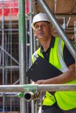 Construction Foreman Builder on Building Site With Clipboard. Male builder foreman, construction worker or site manager holding a clipboard, wearing a white hard stock photography