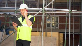 Male builder foreman construction worker on building site talking on cell phone. Male builder foreman, surveyor, worker or architect working on construction stock video footage