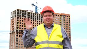 Male builder foreman, worker or architect on construction building site greeting by waving his hand.  stock video footage