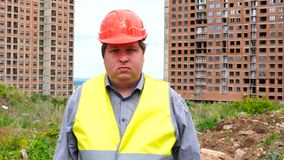 Male builder foreman, worker or architect on construction building site looking at camera emotionless.  stock footage