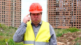 Male builder foreman, worker or architect on construction building site is pointing you are crazy.  stock video