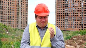 Male builder foreman, worker or architect on construction building site shake hands out of dust. Tired male builder foreman, worker or architect on construction stock footage