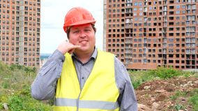Male builder foreman, worker or architect on construction building site showing call me gesture.  stock footage
