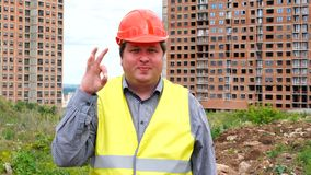 Male builder foreman, worker or architect on construction building site showing okay gesture while smiling to camera.  stock video