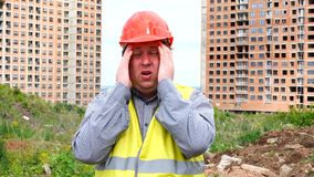 Male builder foreman, worker or architect on construction building site is worried and has a stress, headache concept.  stock footage