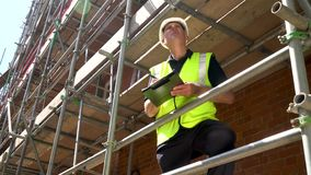 Construction worker on building site standing on scaffolding writing on a clipboard stock footage