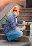 Smiling male builder in hardhat repairing stone stairs. Male builder in hardhat repairing stone stairs Royalty Free Stock Images
