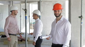 Male builder holds set of plans of building under construction stock video footage