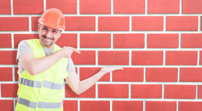 Male builder indicate towards his empty hand Royalty Free Stock Photo