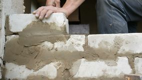 Male builder laying white brick on cement and standing wall. Hands of man laying building bricks close up view. Male builder laying white brick on cement and stock footage