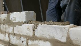 Male builder laying white brick on cement and standing wall. Hands of man laying building bricks close up view. Male builder laying white brick on cement and stock video footage