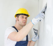 Male builder repairs wall Stock Photo