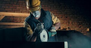 Male builder in respirator using angle grinder
