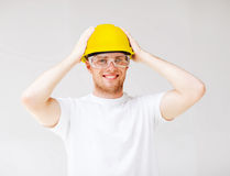 Male builder in safety glasses and yellow helmet. Building, developing, consrtuction and architecture concept - picture of male builder in safety glasses and Stock Image