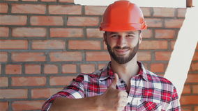 Male builder shows his thumb up. Male builder showing his thumb up at the building under construction. Bearded man in orange hard hat standing against background stock footage