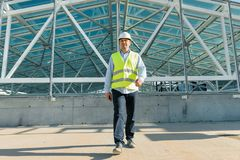 Male builder walking forward on the roof of construction site. Building, development concept.  royalty free stock image