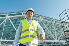 Male builder walking forward on the roof of construction site. Building, development concept.  stock images