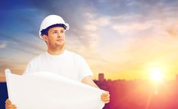 Male builder in white hard hat with blueprint. Construction, building and people concept - male builder or foreman in white hard hat with blueprint over city Stock Photo
