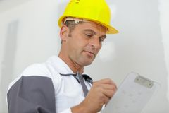 Male builder writing on clipboard royalty free stock images