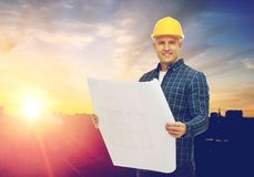 Male builder in yellow hard hat with blueprint. Construction, building and people concept - male builder in yellow hard hat with blueprint over city background Royalty Free Stock Photography
