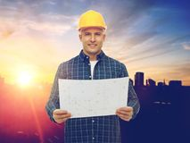 Male builder in yellow hard hat with blueprint. Construction, building and people concept - male builder in yellow hard hat with blueprint over city background Stock Photo
