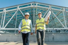 Male builders go forward on roof of construction site. Building, development, teamwork and people concept.  stock photography