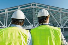 Male builders on roof of construction site,back view. Building, development, teamwork and people concept.  royalty free stock image