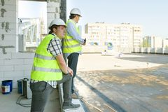 Male builders on the roof of construction site. Building, development, teamwork and people concept.  royalty free stock photography
