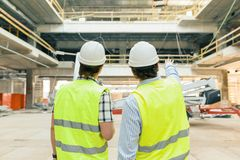 Male building workers working at construction site, back view. Building, development, teamwork and people concept.  stock image