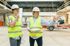 Male building workers working at construction site. Building, development, teamwork and people concept.  stock photography