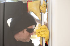 Burglar breaking through window of house. Male burglar with black hood, gloves and sunglasses trying to break in residential house, home, through window, with stock image