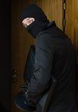 Male burglar in mask stealing TV Stock Image
