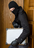Male burglar stealing case Royalty Free Stock Image