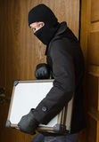 Male burglar stealing case Royalty Free Stock Images