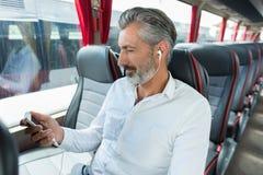 Male bus passenger charging cellphone stock image