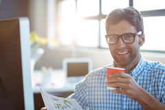 Male business executive holding newspaper while having coffee Stock Photo
